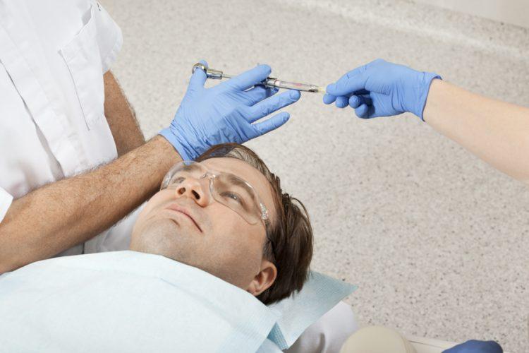Ryc. 11 b. Jednym z najbardziej kluczowych momentów dla ograniczenia stresu pacjenta jest chwila, kiedy lekarz sięga po przygotowaną karpulę lub odbiera ją z rąk asystentki. Najważniejszym elementem jest utrzymanie karpuli z odbezpieczoną igłą cały czas poza linią wzroku pacjenta. Zaleca się, aby procedura uchwycenia dłonią gotowej karpuli oraz ruch przysunięcia jej do twarzy pacjenta przebiegały nad klatką piersiową pacjenta lub za jego głową.