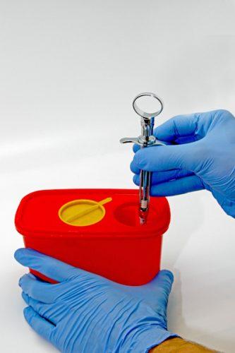 Ryc. 17 a. Po zakończonym podawania leku znieczulającego miejscowo i usunięciu igły z tkanek miękkich należy ją bez dotykania palcami odkręcić wewnątrz pojemnika twardościennego (umożliwiają to specjalne ząbki) lub bez odkręcania bezpośrednio spalić do poziomu plastykowej nasadki w specjalnej spalarce.